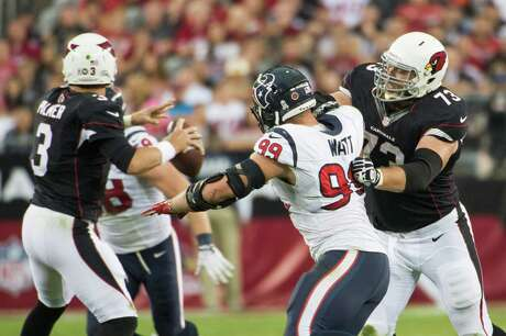 Cardinals tackle Eric Winston (73) tries to keep Texans defensive end J.J. Watt away from quarterback Carson Palmer, and with good reason. Watt had four tackles and a sack and caused and recovered two fumbles.