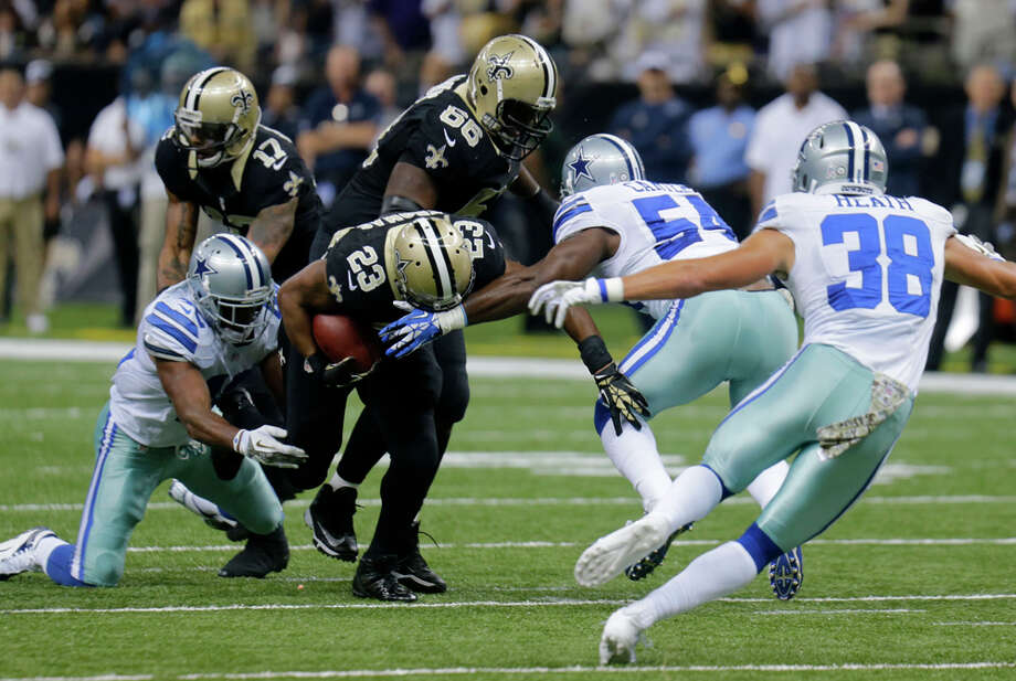 New Orleans Saints running back Pierre Thomas (23) carries between Dallas Cowboys free safety Barry Church (42) and outside linebacker Bruce Carter (54) in the first half of an NFL football game in New Orleans, Sunday, Nov. 10, 2013. (AP Photo/Bill Haber) Photo: Bill Haber, Associated Press / FR170136 AP