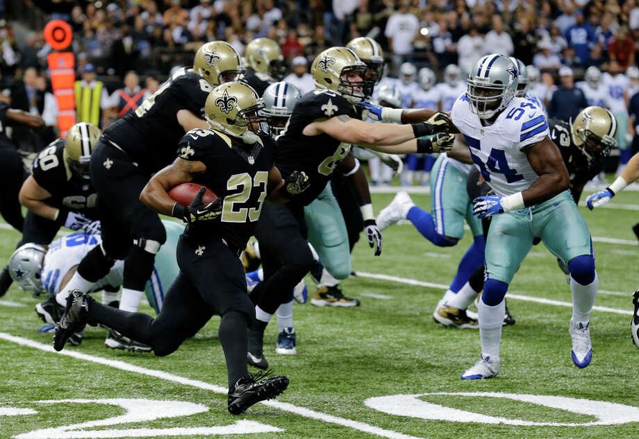 New Orleans Saints running back Pierre Thomas (23) carries past Dallas Cowboys outside linebacker Bruce Carter (54) in the first half of an NFL football game in New Orleans, Sunday, Nov. 10, 2013. (AP Photo/Bill Haber) Photo: Bill Haber, Associated Press / FR170136 AP