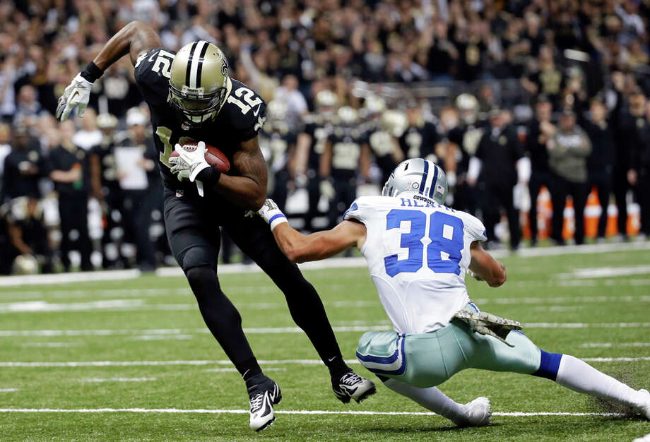 New Orleans Saints wide receiver Marques Colston (12) eludes Dallas Cowboys defensive back Jeff Heath (38) on a touchdown reception in the first half of an NFL football game in New Orleans, Sunday, Nov. 10, 2013. (AP Photo/Dave Martin) Photo: Dave Martin, Associated Press / AP
