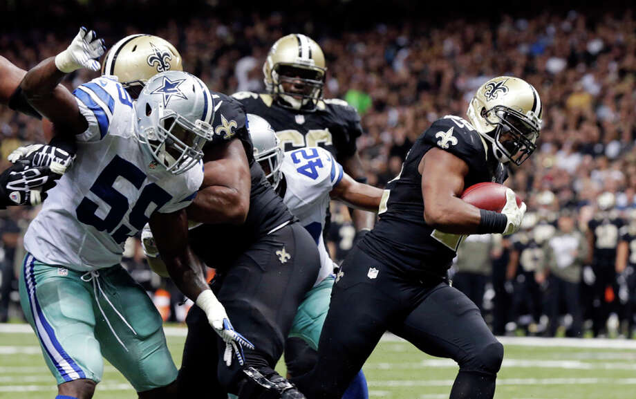 New Orleans Saints running back Mark Ingram, right, carries into the end zone in front of Dallas Cowboys inside linebacker Ernie Sims (59) and free safety Barry Church (42) on a touchdown carry in the second half of an NFL football game in New Orleans, Sunday, Nov. 10, 2013. (AP Photo/Dave Martin) Photo: Dave Martin, Associated Press / AP