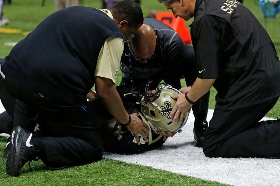 New Orleans Saints tight end Benjamin Watson (82) is tended to after landing on his head on a  pass play in the second half of an NFL football game against the Dallas Cowboys in New Orleans, Sunday, Nov. 10, 2013. (AP Photo/Bill Haber) Photo: Bill Haber, Associated Press / FR170136 AP