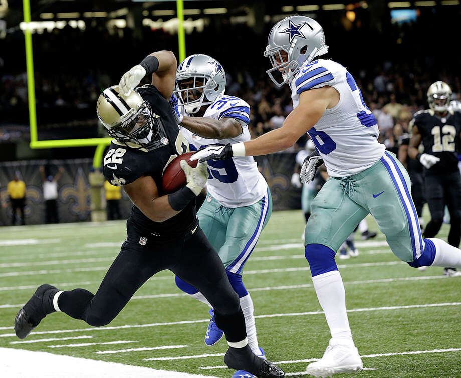 New Orleans Saints running back Mark Ingram (22) is forced out of bounds by Dallas Cowboys cornerback Brandon Carr (39) and defensive back Jeff Heath in the second half of an NFL football game in New Orleans, Sunday, Nov. 10, 2013. (AP Photo/Dave Martin) Photo: Dave Martin, Associated Press / AP