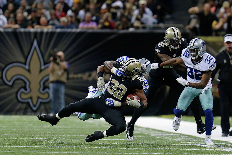 Dallas Cowboys inside linebacker Ernie Sims grabs the face mask of New Orleans Saints running back Mark Ingram (22) in the second half of an NFL football game in New Orleans, Sunday, Nov. 10, 2013. (AP Photo/Bill Haber) Photo: Bill Haber, Associated Press / FR170136 AP