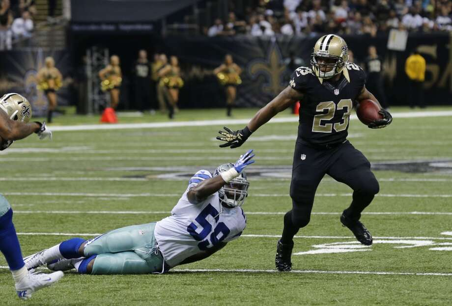 New Orleans Saints running back Pierre Thomas (23) rushes past Dallas Cowboys inside linebacker Ernie Sims (59) in the first half of an NFL football game in New Orleans, Sunday, Nov. 10, 2013. (AP Photo/Bill Haber) Photo: Associated Press