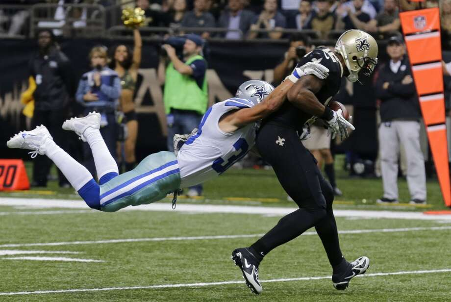 Dallas Cowboys defensive back Jeff Heath (38) tries to tackle New Orleans Saints wide receiver Marques Colston (12) on a touchdown reception in the first half of an NFL football game in New Orleans, Sunday, Nov. 10, 2013. (AP Photo/Bill Haber) Photo: Associated Press