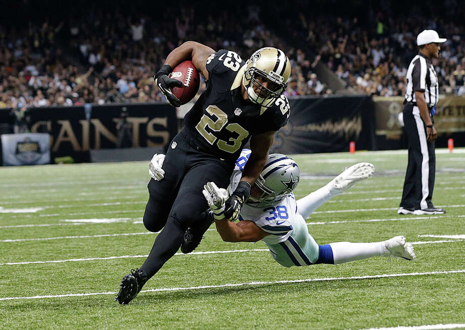 New Orleans Saints running back Pierre Thomas (23) carries against defensive back Jeff Heath (38) on a touchdown carry in the first half of an NFL football game in New Orleans, Sunday, Nov. 10, 2013. (AP Photo/Dave Martin) Photo: Dave Martin, Associated Press / AP