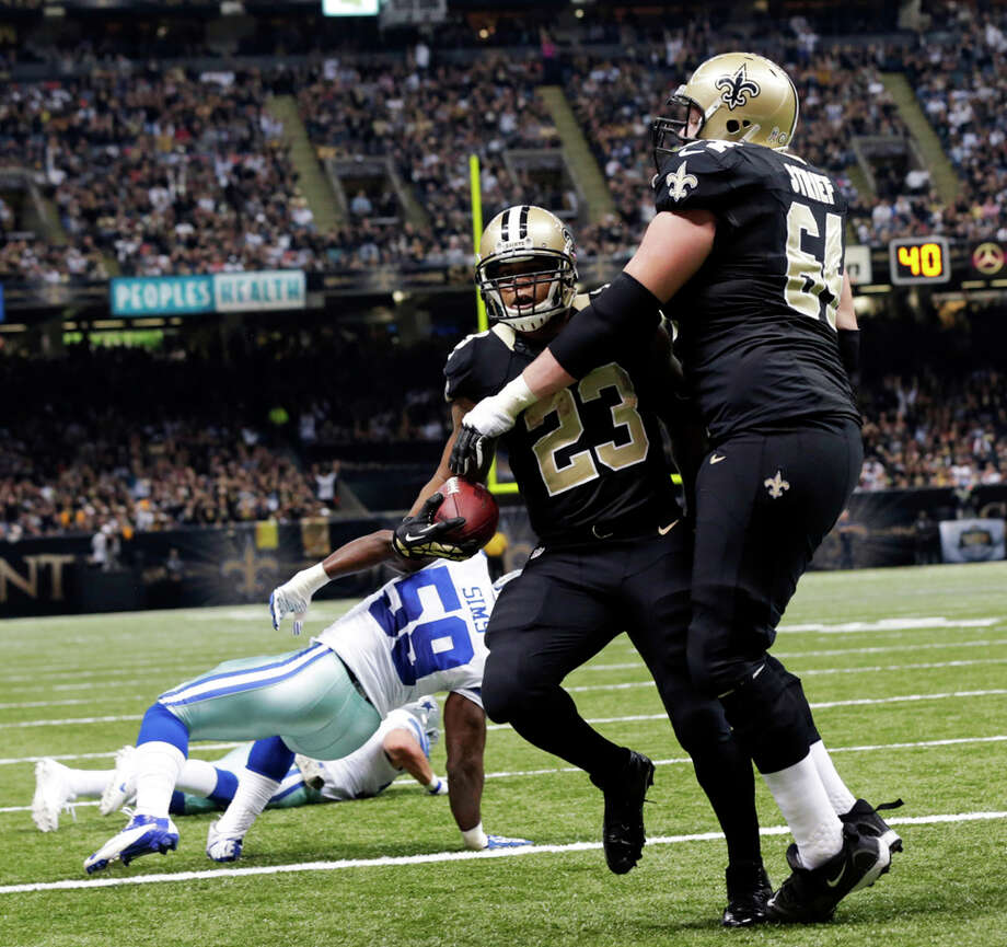 New Orleans Saints running back Pierre Thomas (23) crosses into the end zone for a touchdown between tackle Zach Strief (64) and Dallas Cowboys inside linebacker Ernie Sims (59) in the first half of an NFL football game in New Orleans, Sunday, Nov. 10, 2013. (AP Photo/Dave Martin) Photo: Dave Martin, Associated Press / AP