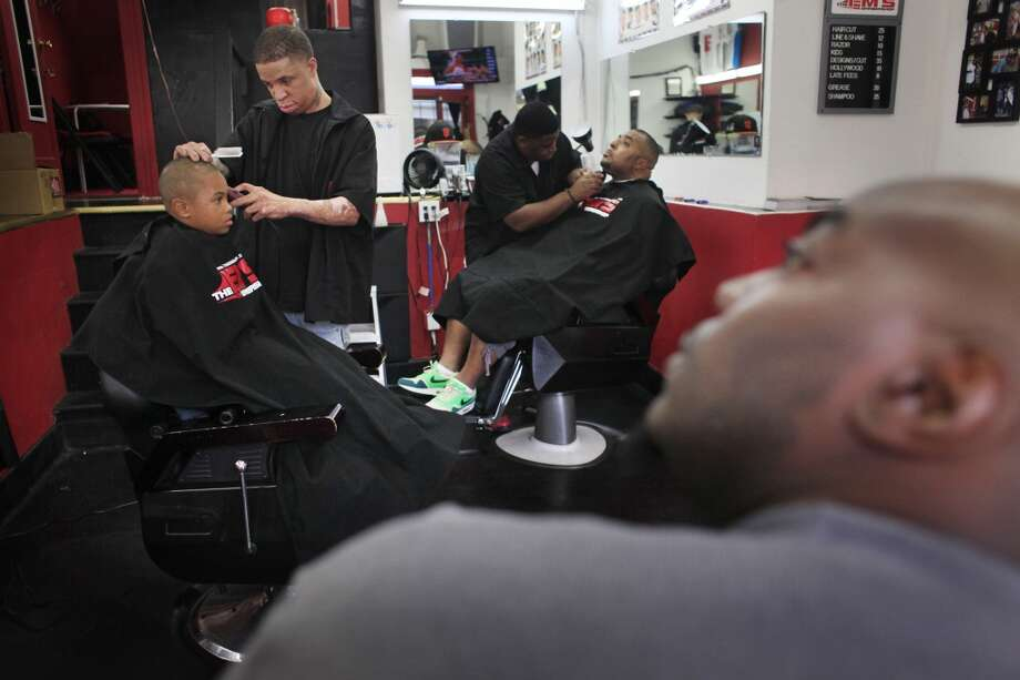 "Emory ""Em"" Waite perfects a cut on  Treasure Mpanda Jr., 7, in his shop ""The Em's Barber Shop"" in San Francisco, Calif. Fifiteen years ago, Waite was burned on 90% of his body. ""I wasn't supposed to survive,"" he said. Photo: Mike Kepka, The Chronicle"