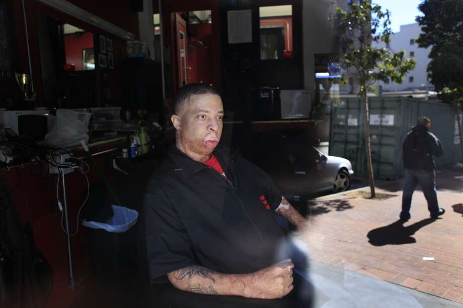"Emory ""Em"" Waite sits in his 10-month-old shop, ""The Em's Barber Shop,"" on Jones Street in San Francisco, Calif. Fifiteen years ago, Waite was burned on 90% of his body. ""I wasn't supposed to survive,"" he said. Photo: Mike Kepka, The Chronicle"