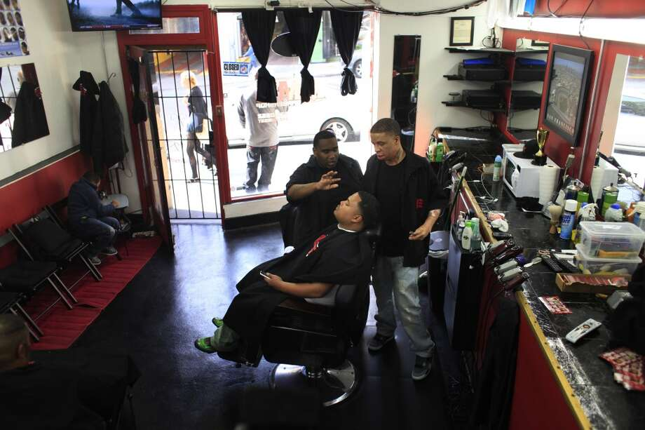 "Emory ""Em"" Waite goes over the final cut with his client Jace Bell in his shop ""The Em's Barber Shop"" in San Francisco, Calif. Photo: Mike Kepka, The Chronicle"