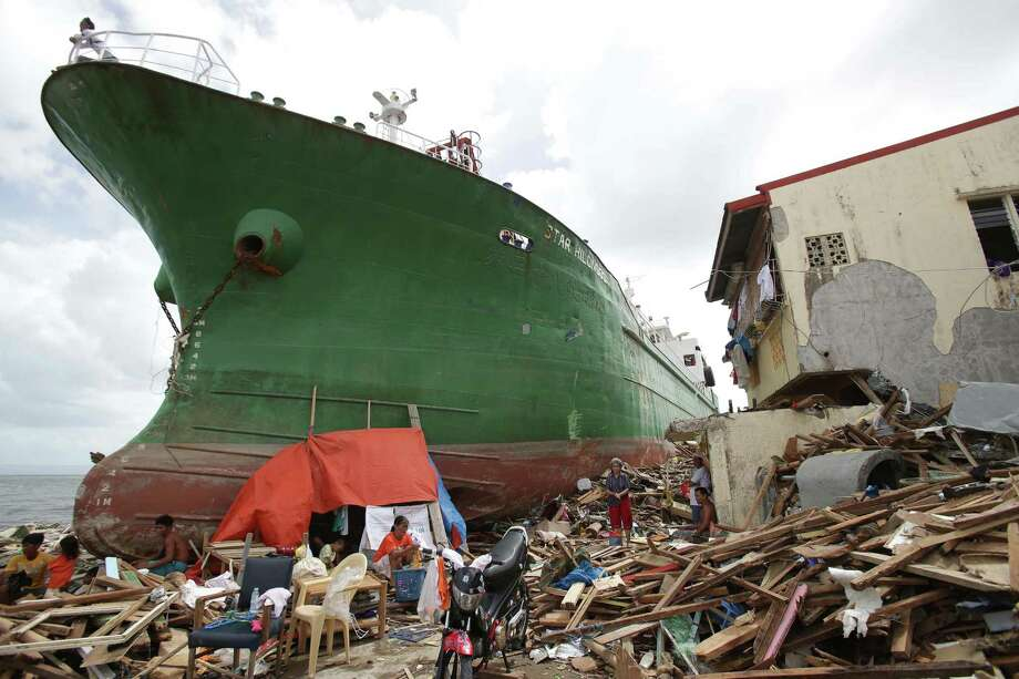 Survivors stay beside a ship that was washed ashore hitting makeshift houses near an oil depot in Tacloban city, Leyte province central Philippines on Monday, Nov. 11, 2013. Authorities said at least 2 million people in 41 provinces had been affected by Friday's typhoon Haiyan and at least 23,000 houses had been damaged or destroyed. Photo: Aaron Favila, AP / AP