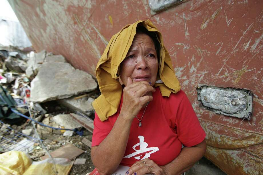 A survivor cries as she tells her ordeal beside a ship that was washed ashore in Tacloban city, Leyte province central Philippines on Monday, Nov. 11, 2013. Authorities said at least 2 million people in 41 provinces had been affected by Friday's typhoon Haiyan and at least 23,000 houses had been damaged or destroyed. Photo: Aaron Favila, AP / AP
