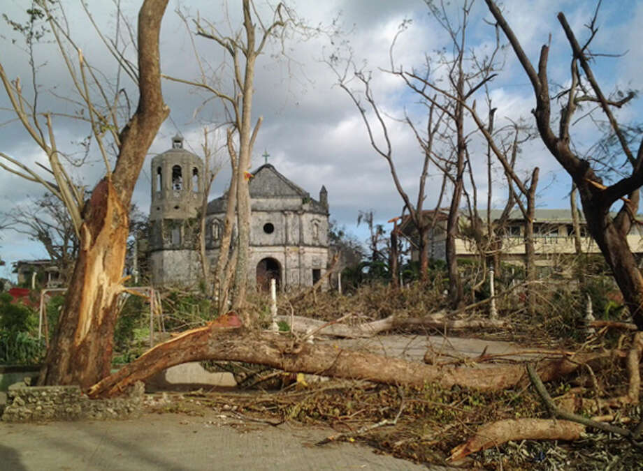 A road to the St. Rose of Lima Parish in Daanbantayan town, the northernmost town of Cebu province, is strewn with debris, Sunday, Nov. 10, 2013, two days after the Typhoon Haiyan hit the Philippines. Rescuers faced blocked roads and damaged airports on Monday as they raced to deliver desperately needed tents, food and medicines to the typhoon-devastated eastern Philippines where thousands are believed dead. Photo: Aledel Cuizon, AP / AP
