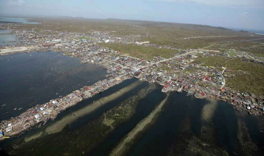 An aerial shot from a Philippine Air Force helicopter shows the devastation Monday Nov. 11, 2013 of the first landfall by typhoon Haiyan in Guiuan, Eastern Samar province, central Philippines. Typhoon Haiyan, one of the most powerful typhoons ever recorded, slammed into central Philippine provinces Friday leaving a wide swath of destruction and socres of people dead. Photo: Bullit Marquez, AP / AP