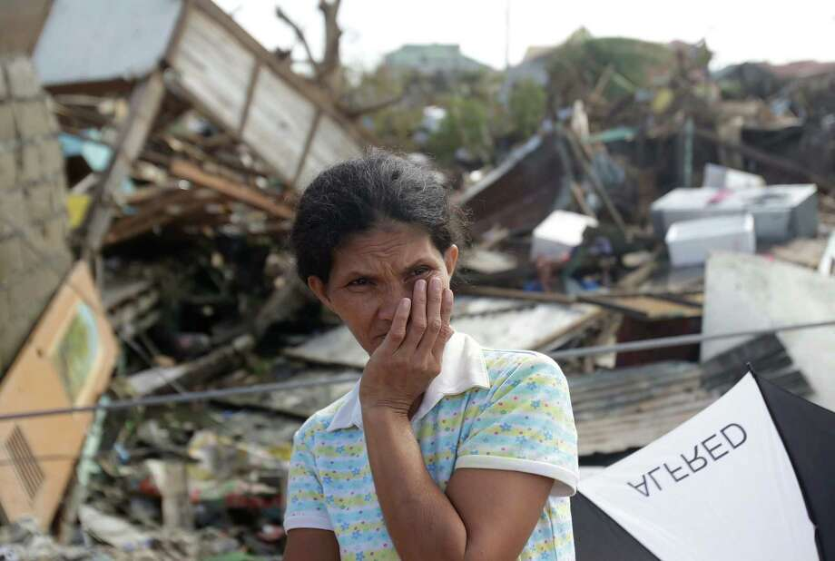 A survivor stands outside her damaged house at typhoon ravaged Tacloban city, Leyte province, central Philippines on Monday, Nov. 11, 2013. Authorities said at least 2 million people in 41 provinces had been affected by Friday's disaster and at least 23,000 houses had been damaged or destroyed. Photo: Aaron Favila, AP / AP