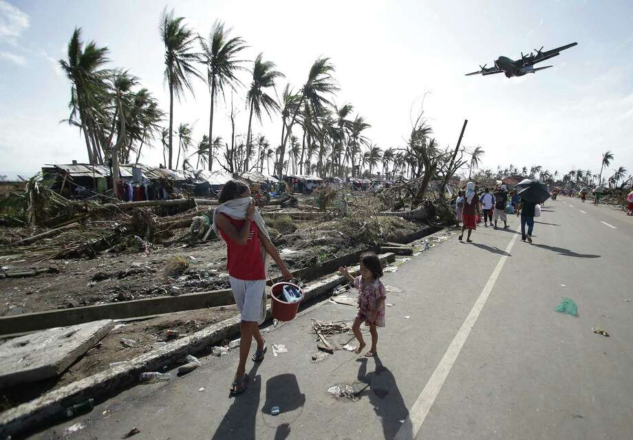 Survivors look at a military C-130 plane which arrives at typhoon-ravaged Tacloban city, Leyte province central Philippines on Monday, Nov. 11, 2013. Stunned survivors of one of the most powerful typhoons ever to make landfall picked through the remains of their homes Monday and pleaded for food and medicine as the Philippines struggled to deal with what is likely its deadliest natural disaster. Photo: Aaron Favila, AP / AP