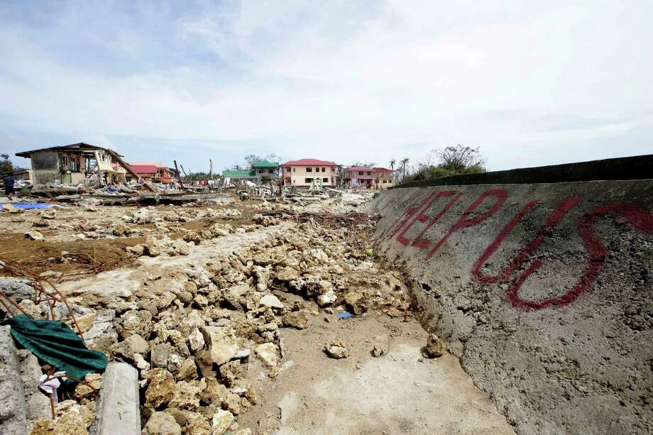 A message is scribbled on the sea wall amidst the devastation brought about by Friday's typhoon Haiyan which lashed Hernani township, Eastern Samar province, central Philippines. Typhoon Haiyan, one of the most powerful typhoons ever recorded, slammed into central Philippine provinces Friday leaving a wide swath of destruction and hundreds of people dead. Photo: Bullit Marquez, AP / AP