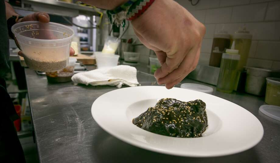 Sesame seeds being sprinkled onto the Chicken with Mole sauce at La Urbana in San Francisco. Photo: John Storey, Special To The Chronicle