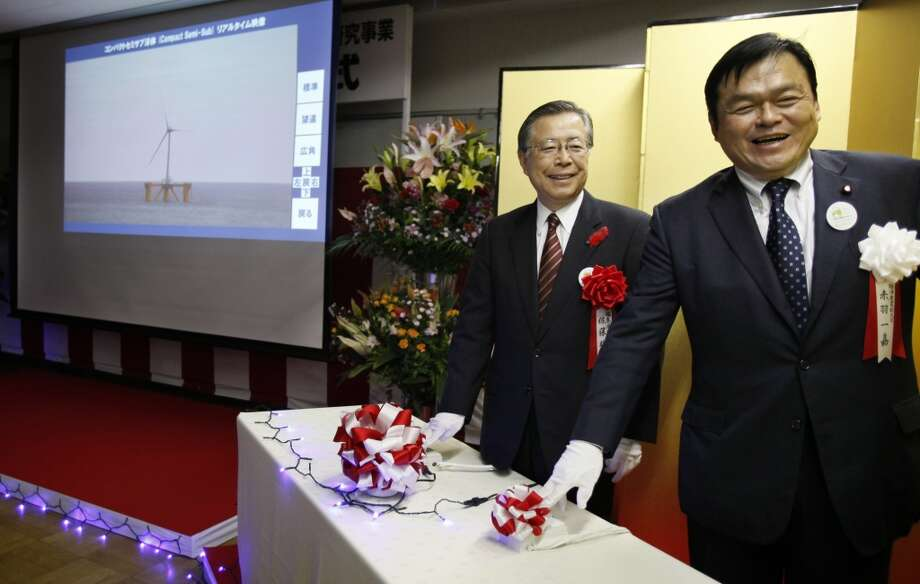 Japan's State Minister of Economy, Trade and Industry Kazuyoshi Akaba (right) and Fukushima Gov. Yuhei Sato push the start button during the launch ceremony of Fukushima Floating Offshore Wind Farm Demonstration Project in Iwaki, Fukushima Prefecture in northeastern Japan, Monday, Nov. 11, 2013. Japan switched on the first turbine at a wind farm 20 kilometers (12 miles) off the coast of Fukushima on Monday, feeding electricity to the grid tethered to the tsunami-crippled nuclear plant onshore. The wind farm near the Fukushima Dai-Ichi nuclear power plant is to eventually have a generation capacity of 1 gigawatt from 143 turbines, though its significance is not limited to the energy it will produce. Photo: Koji Sasahara, AP