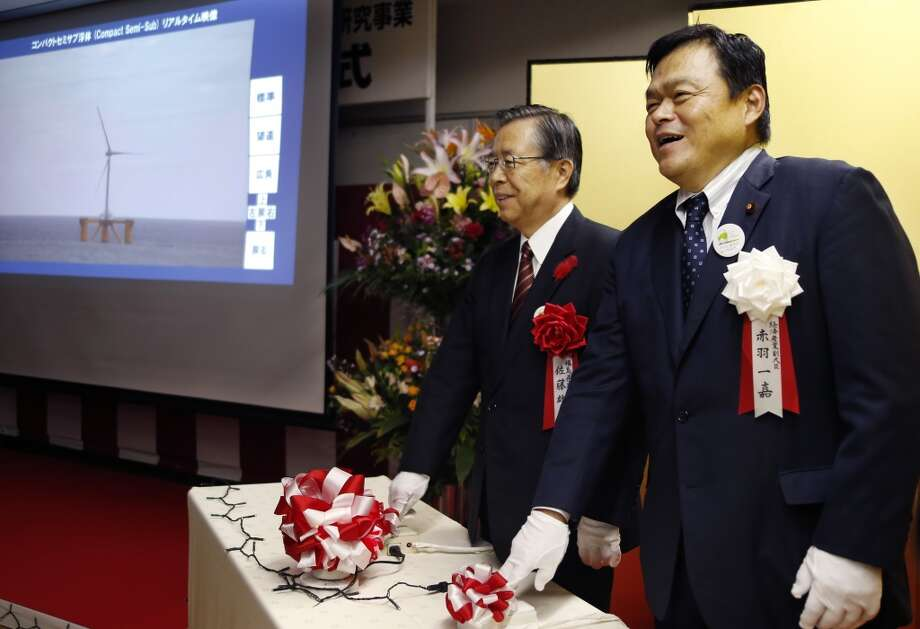 Japan's State Minister of Economy, Trade and Industry Kazuyoshi Akaba (right) and Fukushima Gov. Yuhei Sato push the start button during the launch ceremony of Fukushima Floating Offshore Wind Farm Demonstration Project in Iwaki, Fukushima Prefecture, northeastern Japan, Monday, Nov. 11, 2013. Japan switched on the first turbine at a wind farm 20 kilometers (12 miles) off the coast of Fukushima on Monday, feeding electricity to the grid tethered to the tsunami-crippled nuclear plant onshore. The wind farm near the Fukushima Dai-Ichi nuclear power plant is to eventually have a generation capacity of 1 gigawatt from 143 turbines, though its significance is not limited to the energy it will produce. Photo: Koji Sasahara, AP