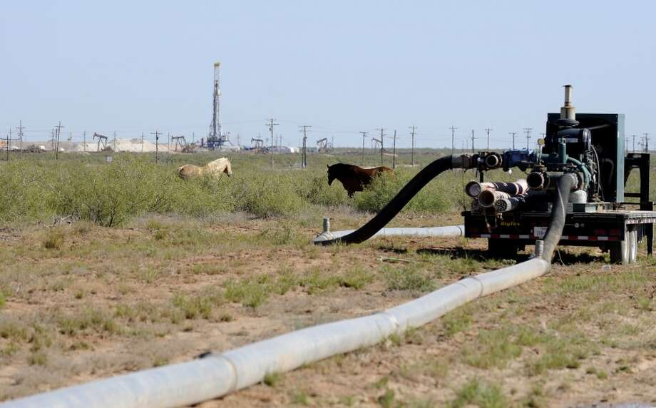 Large hoses go from one hydraulic fracturing drill site to another as horses graze in the field Sept. 24, 2013, in Midland, Texas. The drilling method known as fracking uses huge amounts of high-pressure, chemical-laced water to free oil and natural gas trapped deep in underground rocks. With fresh water not as plentiful companies have been looking for ways to recycle their waste. Photo: Pat Sullivan, AP