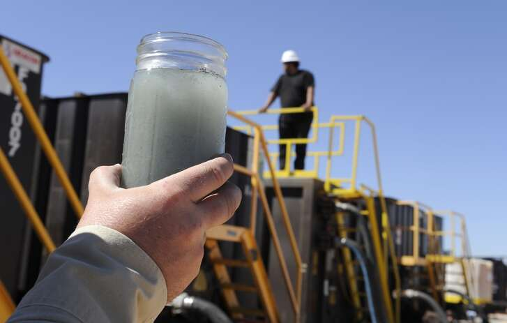 A jar holding waste water from hydraulic fracturing is held up to the light at a recycling site in Midland, Texas, Sept. 24, 2013. The drilling method known as fracking uses huge amounts of high-pressure, chemical-laced water to free oil and natural gas trapped deep in underground rocks. With fresh water not as plentiful companies have been looking for ways to recycle their waste.