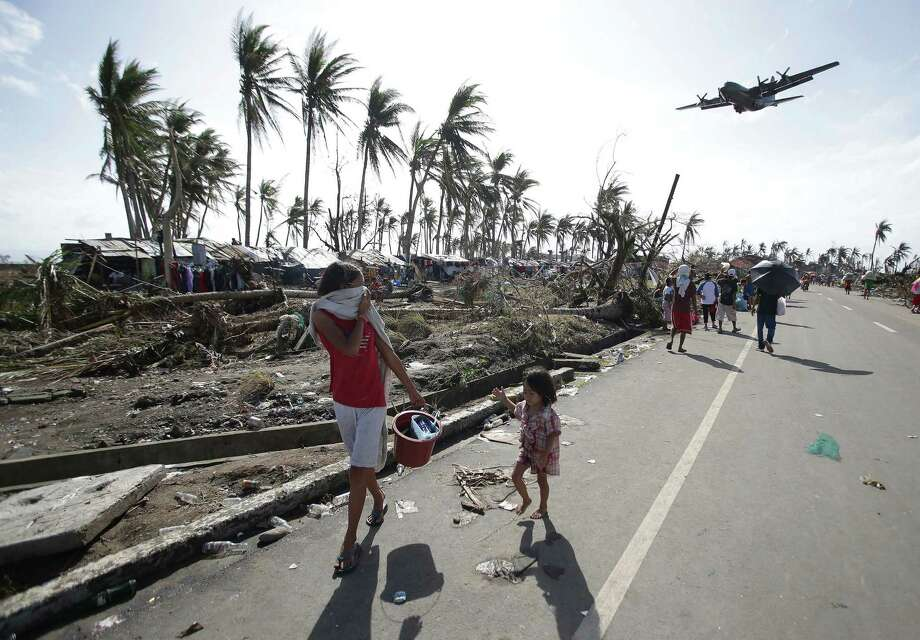 Survivors look up at a military C-130 plane as it arrives at typhoon-ravaged Tacloban city, Leyte province in central Philippines on Monday, Nov. 11, 2013. Stunned survivors of one of the most powerful typhoons ever to make landfall picked through the remains of their homes Monday and pleaded for food and medicine as the Philippines struggled to deal with what is likely its deadliest natural disaster. Photo: Aaron Favila, AP / AP