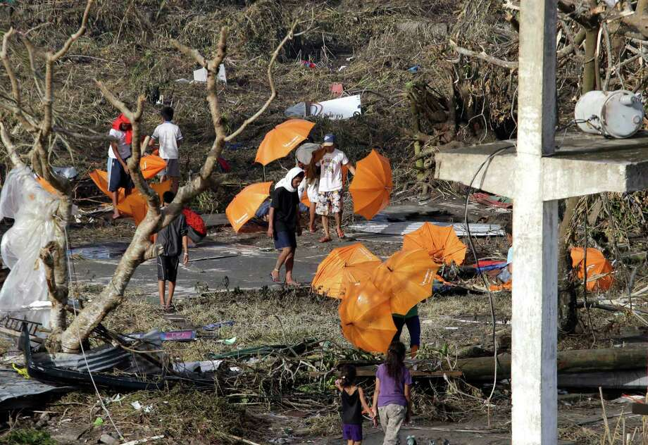Residents retrieve umbrellas prior to lining up for relief supplies at Tacloban airport Monday Nov. 11, 2013, following Friday's typhoon Haiyan that lashed this city and several provinces in central Philippines. Authorities said at least 2 million people in 41 provinces had been affected by Friday's disaster and at least 23,000 houses had been damaged or destroyed. Photo: Bullit Marquez, AP / AP
