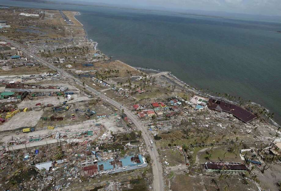 This aerial photo taken from a Philippine Air Force helicopter shows the devastation caused by Typhoon Haiyan in Tacloban city, Leyte province, central Philippines, Monday, Nov. 11, 2013. Typhoon-ravaged Philippine islands faced an unimaginably huge recovery effort that had barely begun Monday, as bloated bodies lay uncollected and uncounted in the streets and survivors pleaded for food, water and medicine. Photo: Bullit Marquez, AP / AP