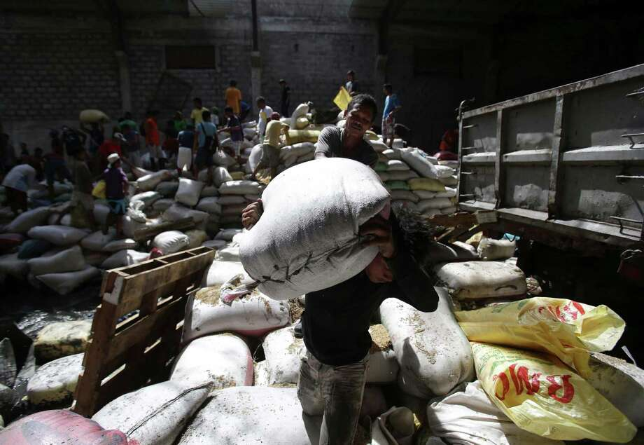 Survivors carry bags of rice from a warehouse which they stormed due to shortage of food at typhoon-ravaged Tacloban city, Leyte province central Philippines on Monday, Nov. 11, 2013. Typhoon-ravaged Philippine islands faced an unimaginably huge relief effort that had barely begun Monday, as bloated bodies lay uncollected and uncounted in the streets and survivors pleaded for food, water and medicine. Photo: Aaron Favila, AP / AP