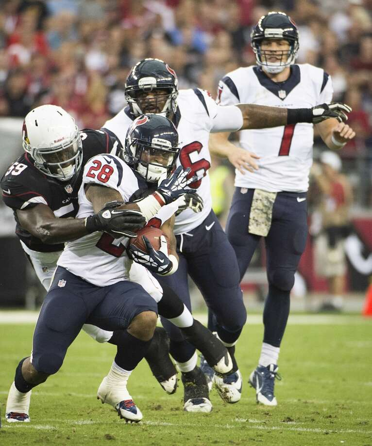 Texans running back Dennis Johnson is wrapped up by Cardinals linebacker Marcus Benard. Photo: Smiley N. Pool, Houston Chronicle