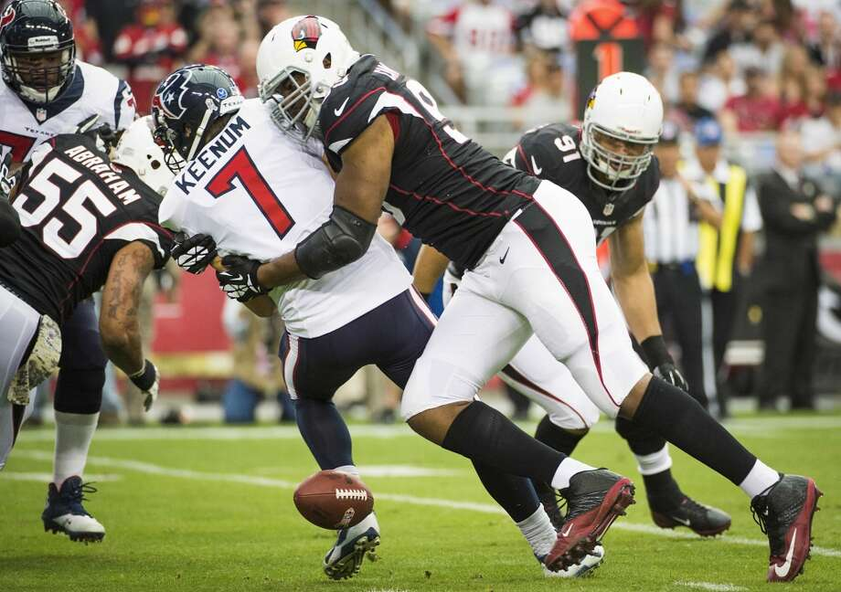 The ball gets away from Texans quarterback Case Keenum as he is hit by Cardinals defensive end Calais Campbell. Photo: Smiley N. Pool, Houston Chronicle