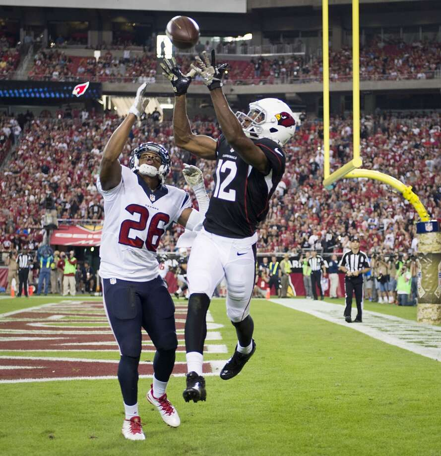 Cardinals wide receiver Andre Roberts (12) reaches up for a pass as Texans defensive back Brandon Harris (26) defends during the second half. Photo: Smiley N. Pool, Houston Chronicle