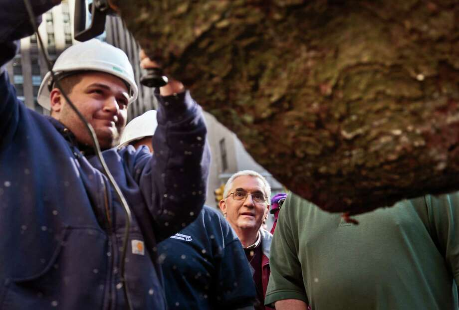 John Vargoshe, center, reacts as Peter Aricola, left, drills a hole into the base of the Rockefeller Center Tree before it is raised and moved to its pedestal  on Friday, Nov. 8, 2013 at Rockefeller Plaza in New York.  The 76-feet tall Norway spruce, donated by the Vargoshe family from Shelton, Conn., is approximately 75 years-old and weighs 12-tons. (AP Photo/Bebeto Matthews) ORG XMIT: NYBM105 Photo: Bebeto Matthews, AP / AP