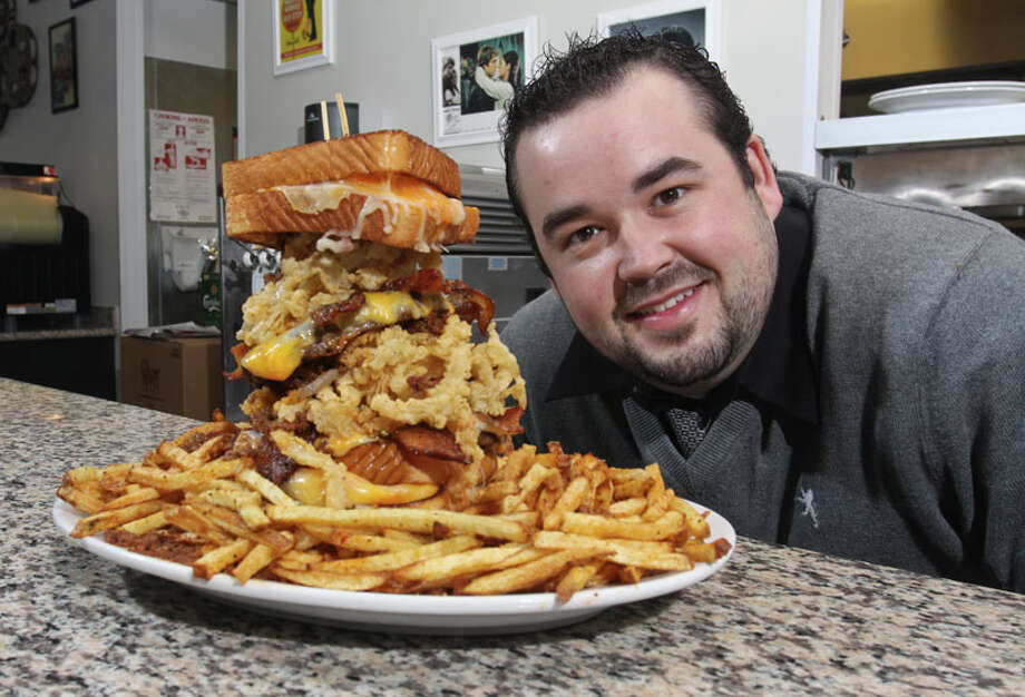 Kevin Goeser, assistant general manager and part owner at Ripps Grille, with one of their Animal House sandwiches, which is two 1/2 pound beef patties, Ripps chili, bacon, and fried onion rings sandwiched between two grilled cheese sandwiches with a massive side of fires. Photo: Gary Fountain, For The Chronicle / Copyright 2011 Gary Fountain