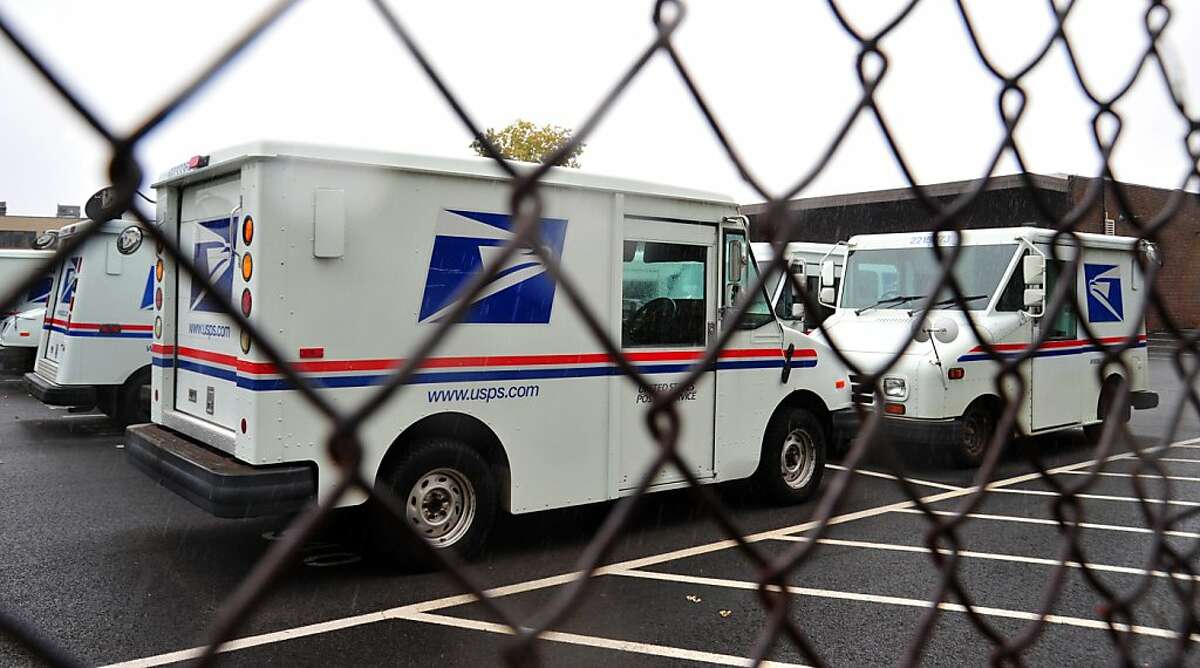 """(FILES)US Postal Service mail delivery trucks sit idle at the Manassas Post Office in Virginia in this September 5, 2011 file photo. The US Postal Service has entered a partnership with online retail giant Amazon to deliver its packages on Sundays for the first time. The first deliveries for Amazon """"Prime"""" customers will be in large US metropolitan areas starting in New York and Los Angeles, Amazon said in a statement early November 11, 2013. Amazon """"Prime"""" members pay an annual $75 service fee in exchange for low-cost or free shipping. AFP PHOTO/Karen BLEIERKAREN BLEIER/AFP/Getty Images"""