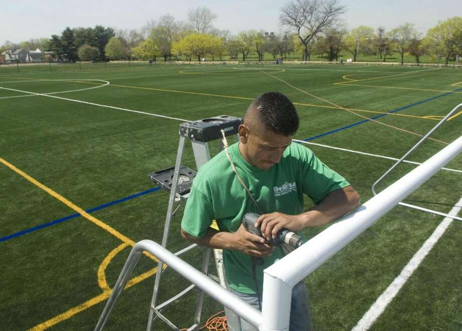 Fernando Castillanos of DeRosa Tennis Court Contractors of Mamaroneck, install goals for the new synthetic turf fields at the West Beach Park in Stamford last year. Lacrosse organizers are hoping to carve out time for the fields. Chris Preovolos/Staff photo Photo: File Photo / Stamford Advocate File Photo