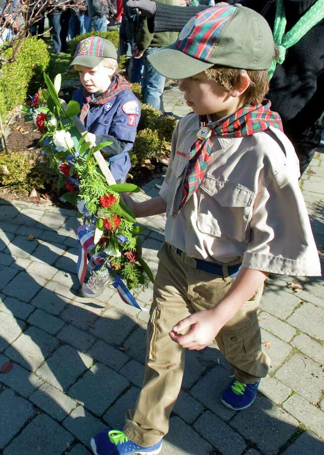 Pack 74 Cub Scouts Henri Vieltojarvi, left, and Nicholas Verbitski, both 9, carry the wreath to the war memorial at the Ridgefield Community Center amidst the Veterans Day ceremony. Monday, Nov. 11, 2013 Photo: Scott Mullin / The News-Times Freelance