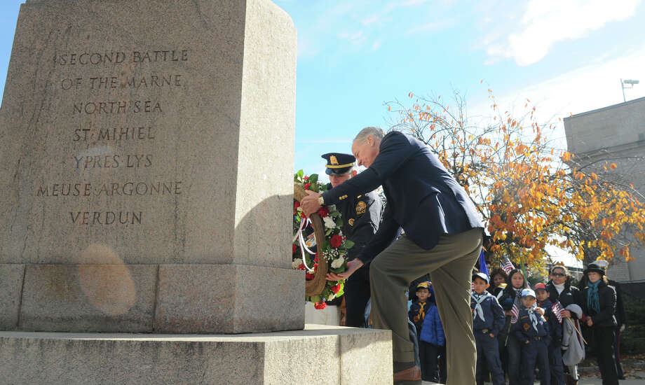 Tom Foley and Lt. Robert Berry, Lt. Col. in the US Army Reserves recently back from a tour in the Middle East, place a wreath on the monument as speaks as the Greenwich American Legion hosts a Veteran's Day ceremony at the war monument on Greenwich Avenue in Greenwich, Conn., Nov. 11, 2013. Photo: Contributed / Stamford Advocate Freelance