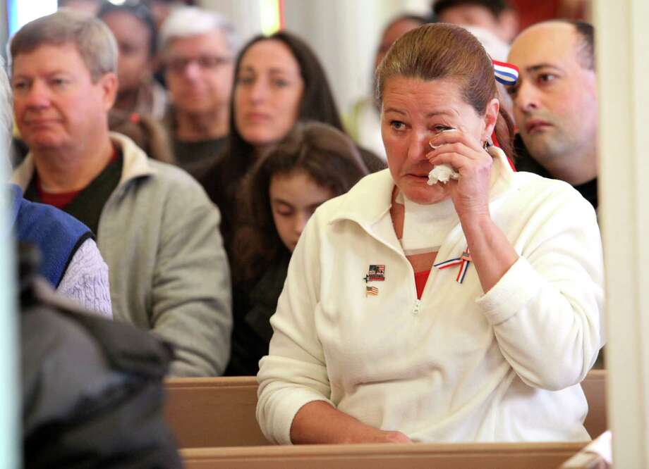 Mary Kristi, right, attends the fourth annual Veterans Day Mass at St Margaret Shrine in Bridgeport, Conn.  on Monday,  November 11, 2013. Photo: BK Angeletti, B.K. Angeletti / Connecticut Post freelance B.K. Angeletti