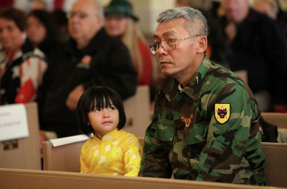 Truc Huynh, 4, and her father, Veteran Phung Huynh attend the fourth annual Veterans Day Mass at St Margaret Shrine in Bridgeport, Conn.  on Monday,  November 11, 2013. Photo: BK Angeletti, B.K. Angeletti / Connecticut Post freelance B.K. Angeletti