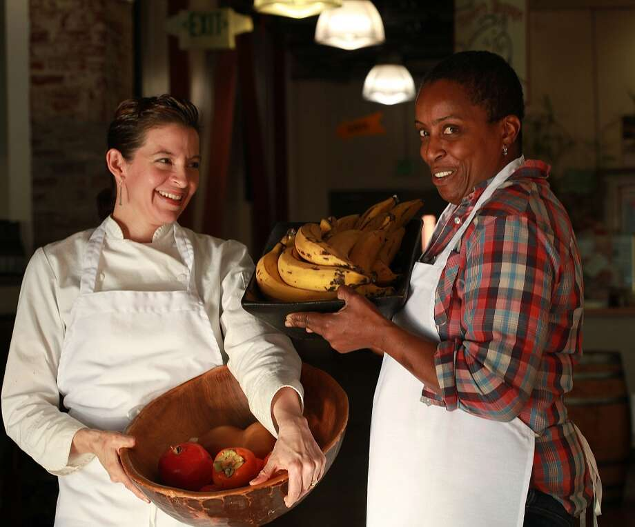Chefs Dominica Rice (left) of Cosecha and Sarah Kirnon (right) of Miss Ollie's carry fruits inside of Old Oakland's historic Swan Market in downtown Oakland. Photo: Liz Hafalia, The Chronicle