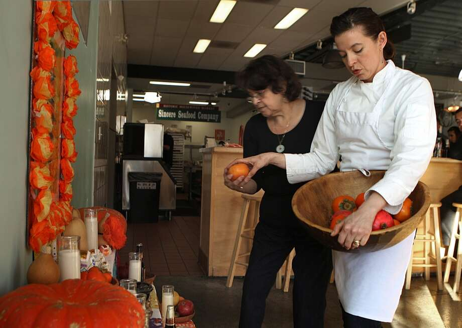 Chef Dominica Rice of Cosecha (right) helps her mother Carmen Marie Rice decorate an altar for D'a de Muertos (Day of the Dead) at her restaurant in Oakland. Photo: Liz Hafalia, The Chronicle