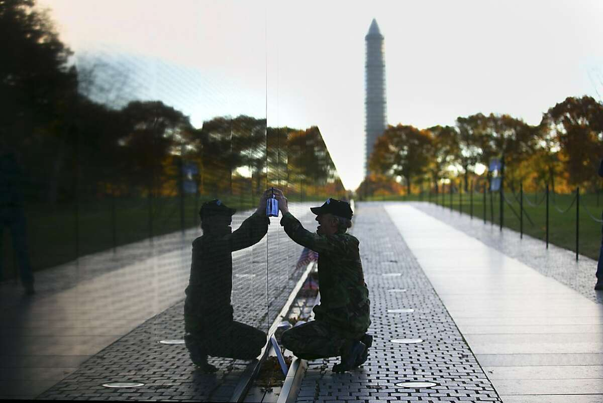 Vietnam veteran Paul Dixon copies the names of his family members who were killed in the Vietnam War, as he makes a sunrise visit to the Vietnam Veterans Memorial Wall in Washington, Nov. 11, 2013.