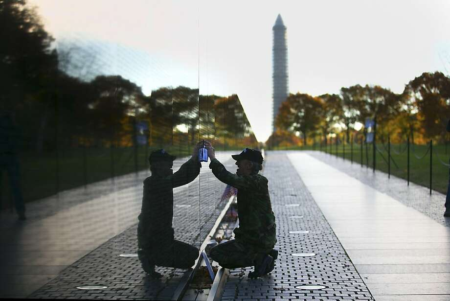 Vietnam veteran Paul Dixon copies the names of his family members who were killed in the Vietnam War, as he makes a sunrise visit to the Vietnam Veterans Memorial Wall in Washington, Nov. 11, 2013. Photo: Doug Mills, New York Times