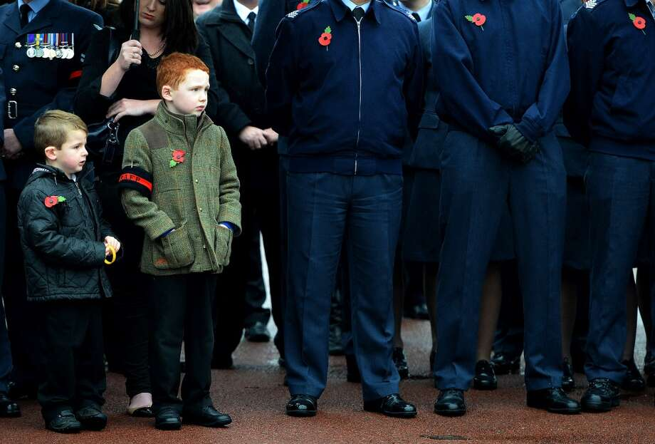 Ethan Brown, 7, and Owen Longdow, 4, attend the funeral of World War II veteran Harold Percival at Lytham Park Cemetery on November 11, 2013 in Lytham St Annes, England. Hundreds of strangers attended the funeral of former RAF Bomber Command ground crew member, Harold Jellicoe Percival, following an online campaign sparked by a notice placed in a newspaper by the funeral directors. Photo: Nigel Roddis, Getty Images