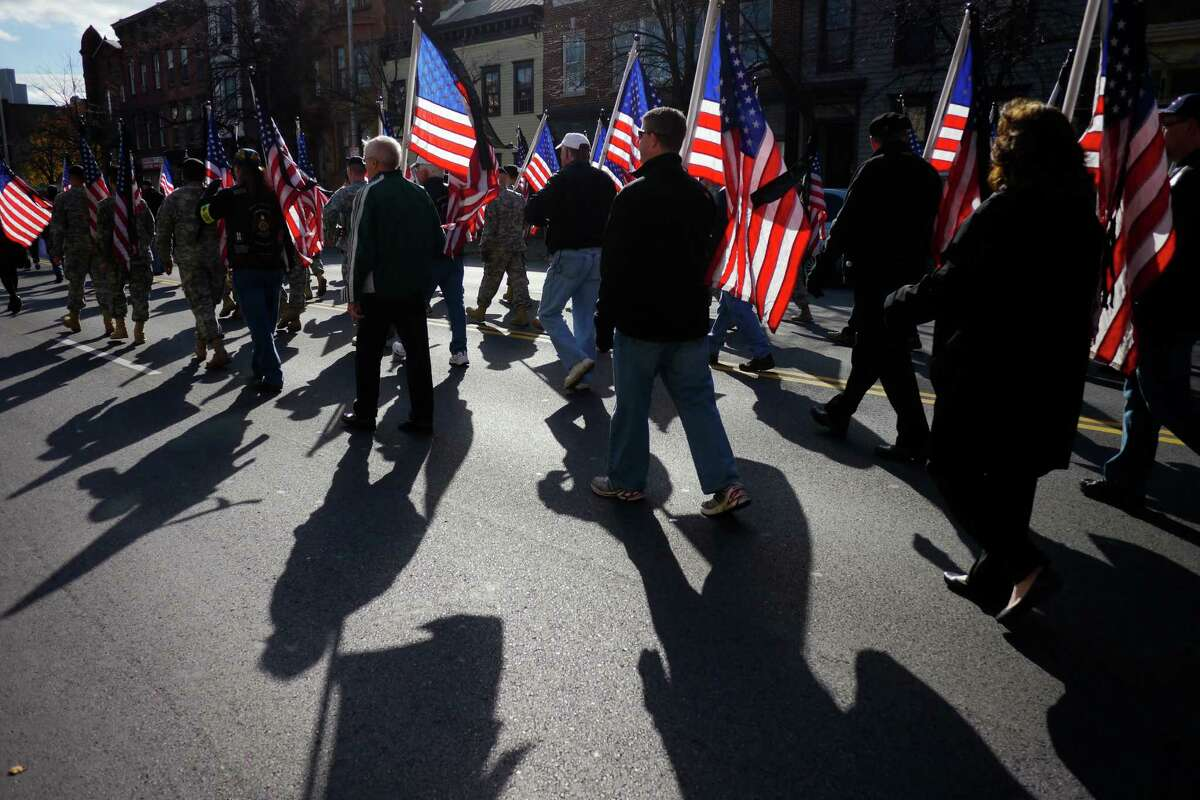 People with the community project Please Remember Me carry flags as they march down Central Avenue during the Veterans Day Parade on Monday, Nov. 11, 2013 in Albany, NY. The Please Remember Me project was started to honor those Capital Region veterans who found and died in conflicts from World War II to the present. (Paul Buckowski / Times Union)