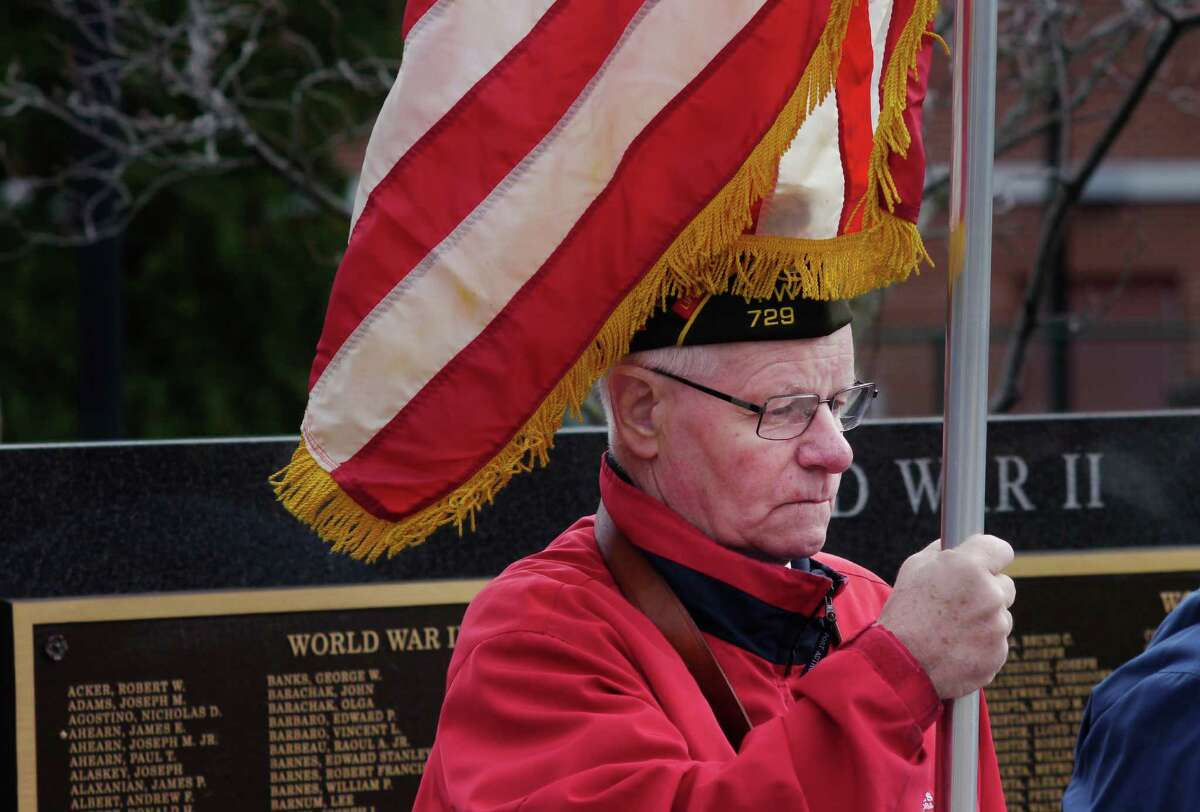 Watervliet VFW Post 729 member Wally Libudziewski holds the American Flag in front of a memorial that bears the names of veterans during a Veterans Day ceremony at Veterans Memorial Park on Monday, Nov. 11, 2013 in Watervliet, NY. A total of 42 names were added to the memorial in the park. The event was put on by the City of Watervliet and the Waterliet VFW Post 729. (Paul Buckowski / Times Union)