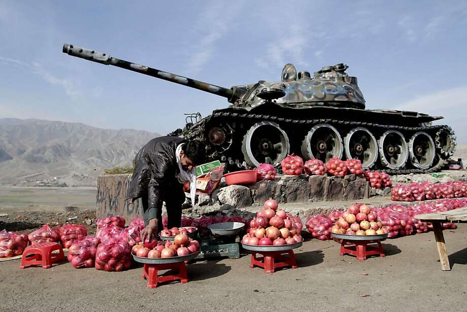 Cannonballs, get yer cannonballs! Mohammad Ajmal sells produce near an old Soviet tank in the Sorubi district of 